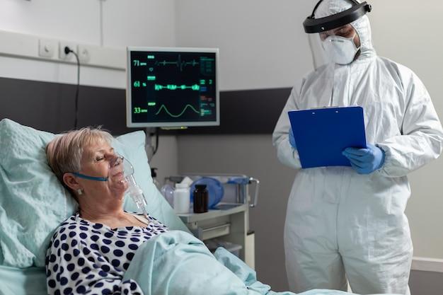 Paciente sênior doente recebendo medicamento intravenoso de uma bolsa de gotejamento iv, deitado na cama, inspira e expira através de máscara de oxigênio, durante a pandemia de coronavírus. médico vestindo terno ppe.
