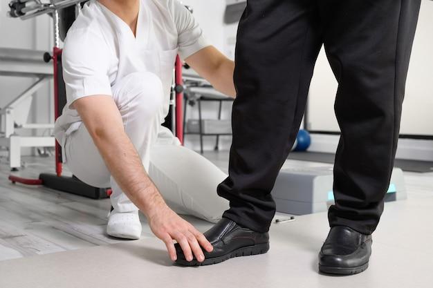 Paciente sênior e fisioterapeuta em exercícios de caminhada de reabilitação.