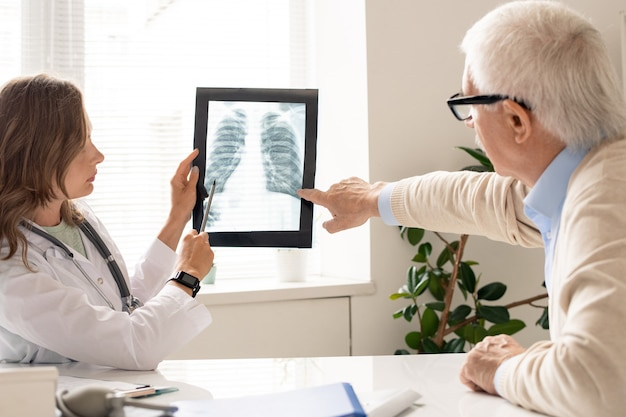 Paciente sênior e jovem pneumologista apontando para uma imagem de raio-x dos pulmões enquanto discutia suas características durante a consulta