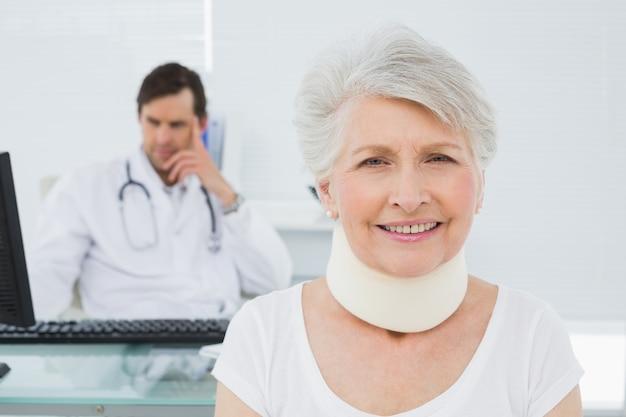 Paciente sênior em colar cirúrgico com médico no escritório