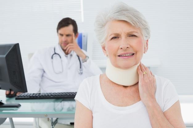 Paciente sênior em coleira cirúrgica com médico em segundo plano no escritório