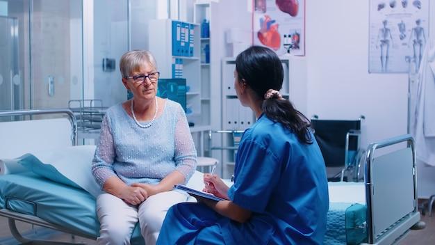 Paciente sênior redired respondendo a perguntas da enfermeira antes da consulta médica em uma moderna instalação de saúde privada. converstation com material médico hospital clínica medicina saúde