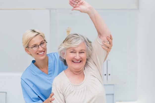 Paciente sênior, sendo, assistido, por, enfermeira, em, levantamento, braço