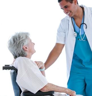 Paciente sênior sentado em uma cadeira de rodas conversando com seu médico