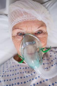 Paciente sênior usando máscara de oxigênio, deitado na cama do hospital