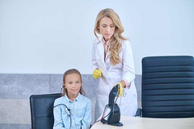 Paciente sentado no consultório médico durante o teste de audiometria