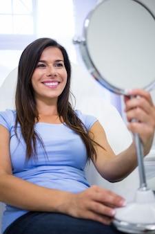 Paciente sorridente, olhando no espelho na clínica