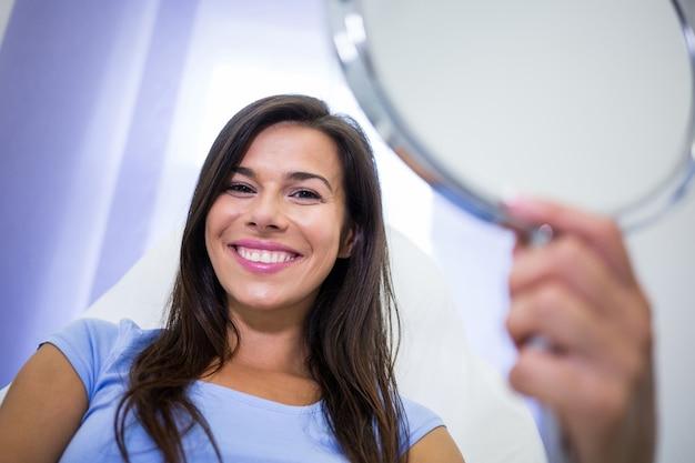 Paciente sorridente segurando um espelho na clínica