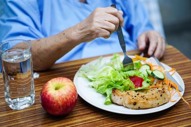 Paciente superior asiático da mulher da senhora idosa que come o alimento saudável do café da manhã no hospital.
