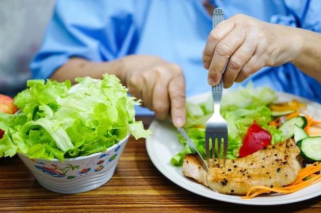 Paciente superior asiático da mulher da senhora idosa que come o café da manhã ao sentar-se no hospital.