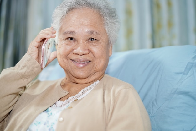 Paciente superior asiático da mulher que fala no telefone celular.