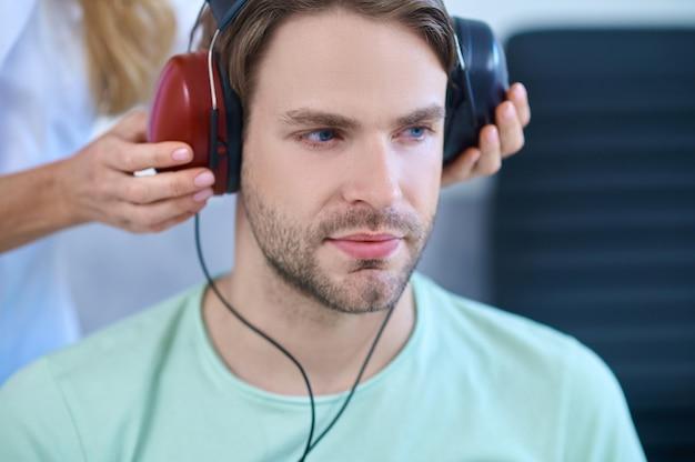 Paciente tranquilo usando fones de ouvido durante um procedimento de triagem auditiva