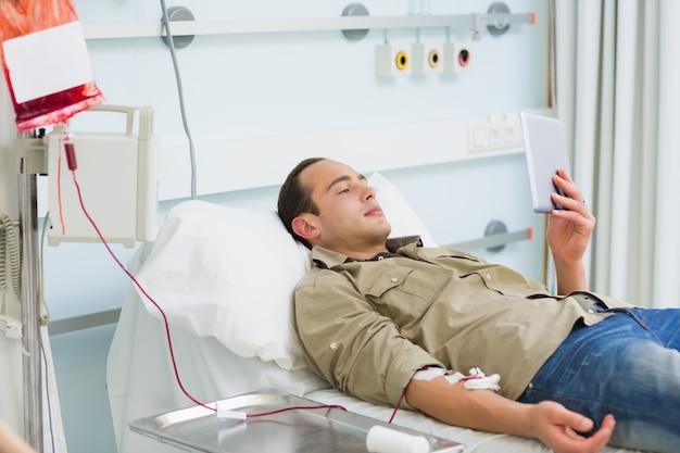 Paciente transfundido olhando para um tablet computador
