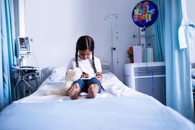 Paciente usando tablet digital na cama