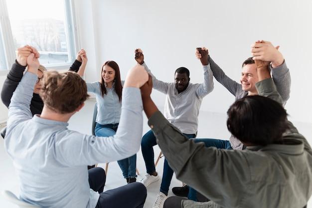 Pacientes de reabilitação sorrindo, levantando as mãos e olhando um ao outro