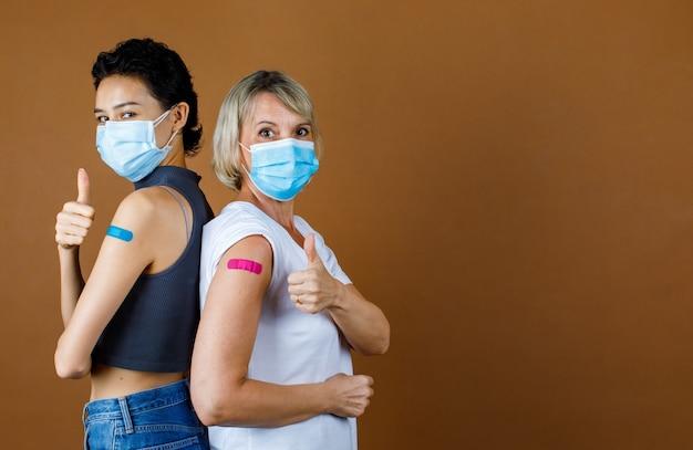 Pacientes do sexo feminino caucasianos usam máscara facial em pé olhar para câmera encostada nas costas mostrando o polegar com gesso colorido juntos após a vacinação na frente do fundo da parede marrom.