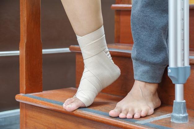 Pacientes do sexo feminino com lesões no tornozelo, ligamentos rasgados e inchaço. usando atadura elástica