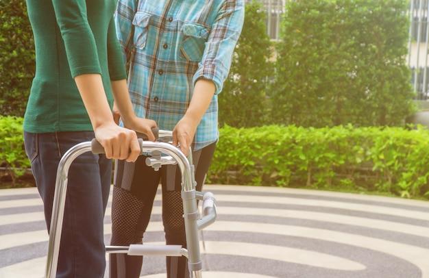 Pacientes do sexo feminino estão caminhando com walker, com fisioterapeuta ajudando e aconselhando.