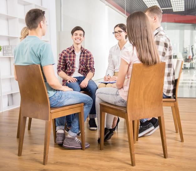 Pacientes em torno de terapeuta contando seus problemas.