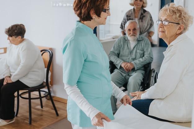 Pacientes idosos e enfermeira em uma casa de repouso local
