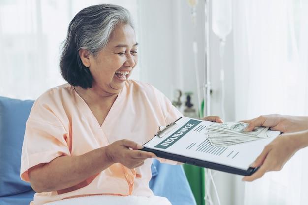 Pacientes idosos ferem mulher na cama do paciente no hospital, segurando-nos notas de dólar, sentem-se felizes em receber dinheiro do seguro de companhias de seguros