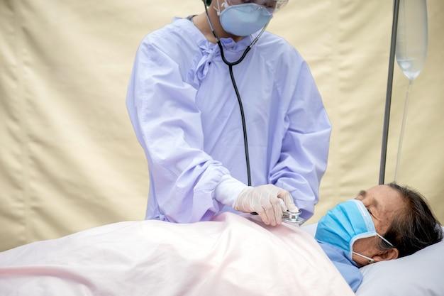 Pacientes idosos ficam na cama, os médicos usam um estetoscópio para verificar a função pulmonar