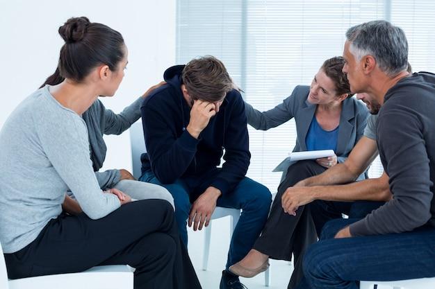 Pacientes preocupados consolando outro no grupo de reabilitação