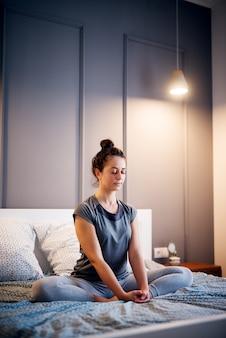 Pacífica bonita meio envelhecida ativa mulher praticando ioga na cama segurando os olhos fechados, sentado no meio exercício de lótus, pose de ardha padmasana e vestindo roupas esportivas à noite.