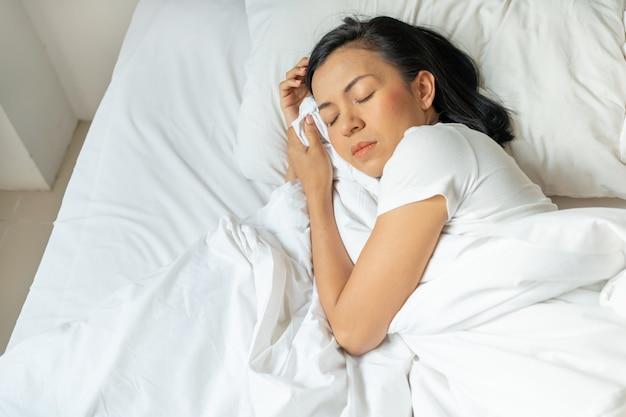 Pacífica e serena jovem usa pijama deitada na cama dormindo.