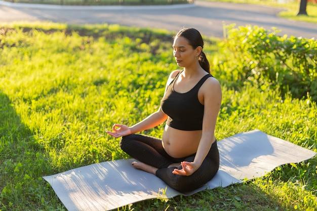 Pacífica jovem grávida positiva em roupa de ginástica faz ioga e medita sentada no tapete