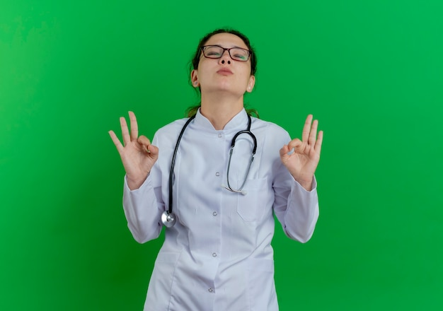 Pacífica jovem médica vestindo túnica médica, estetoscópio e óculos, fazendo sinal de ok com os olhos fechados, isolado na parede verde com espaço de cópia