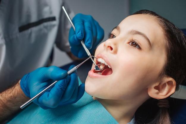 Pacífica menina sentada na cadeira odontológica