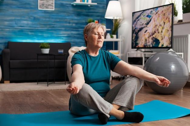 Pacífica mulher sênior com os olhos fechados, sentada na esteira de ioga, meditando durante o treino de bem-estar. pensionista confortável praticando posição de lótus e exercitando concentração corporal na sala de estar