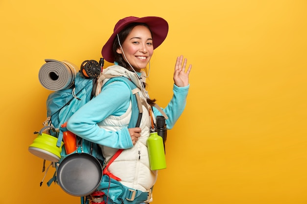 Packpacker mulher asiática sorridente positiva tem uma expressão alegre, acena a palma da mão para a câmera, carrega todas as coisas necessárias em uma mochila grande
