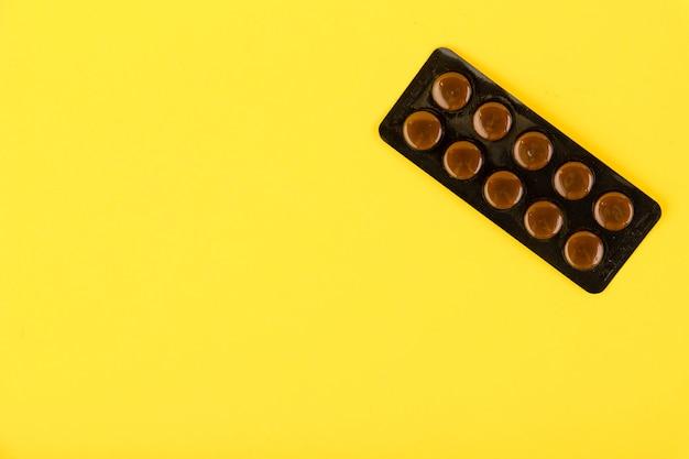 Pacote blister de comprimidos médicos marrons em um fundo amarelo. copie o espaço.