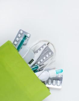 Pacote com comprimidos de medicamentos, sprays, seringas termômetro