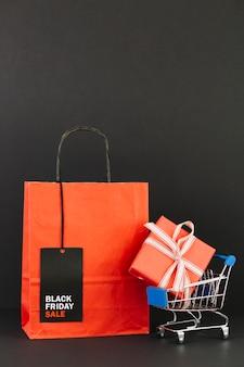 Pacote com tag perto de carrinho de compras com presente