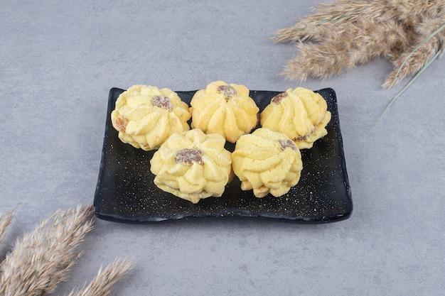 Pacote de biscoitos em uma bandeja ao lado de talos de grama de pena empacotados em mármore