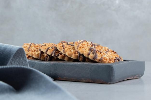 Pacote de biscoitos em uma placa de madeira ao lado da toalha de mesa em fundo de mármore.