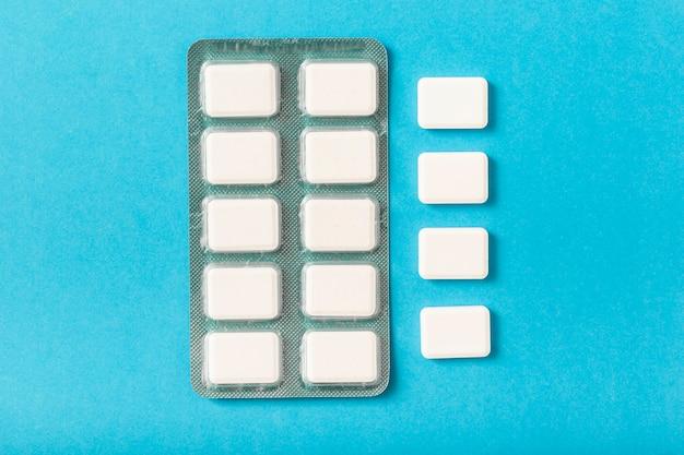 Pacote de bolha de pastilha elástica branca sobre fundo azul