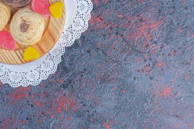 Pacote de bolos e geleias em uma bandeja de madeira na mesa abstrata.