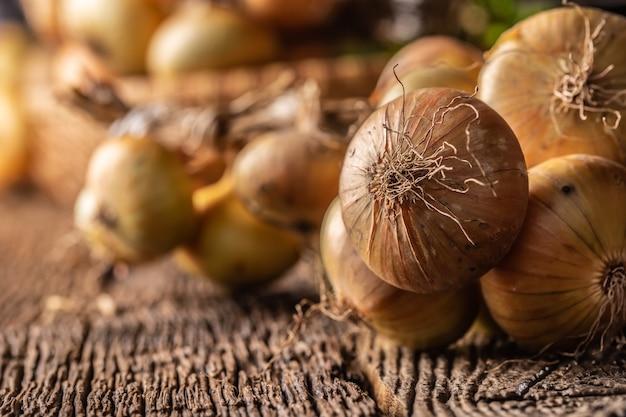 Pacote de cebola seca livremente deitada sobre uma mesa de madeira.