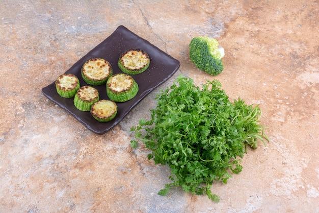 Pacote de coentro, pedaço de brócolis e uma travessa de abobrinha frita na superfície de mármore