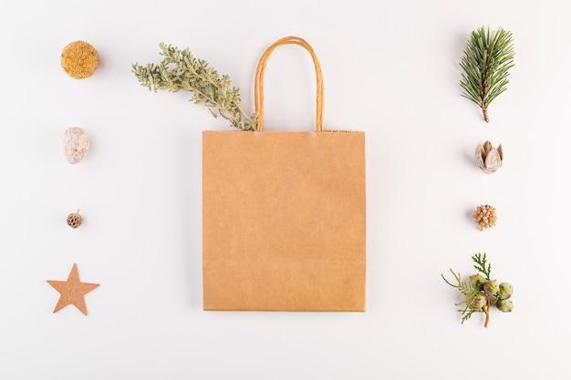 Pacote de compras com galhos de coníferas e conjunto de decorações