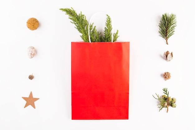 Pacote de compras com galhos de coníferas e conjunto de ornamentos