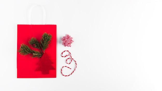 Pacote de compras com ramo de coníferas e enfeite de árvore de abeto