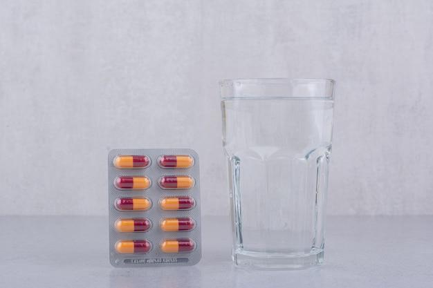Pacote de comprimidos de antibióticos e um copo de água no fundo de mármore. foto de alta qualidade