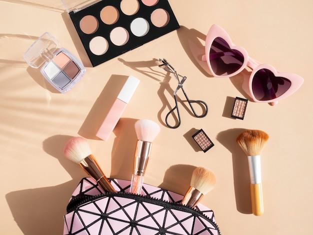 Pacote de cosméticos de beleza com óculos de sol ao lado