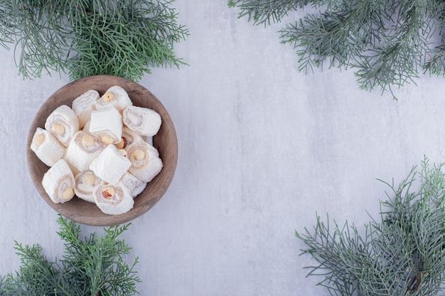 Pacote de delícias turcas e ramos de pinheiro em fundo branco.