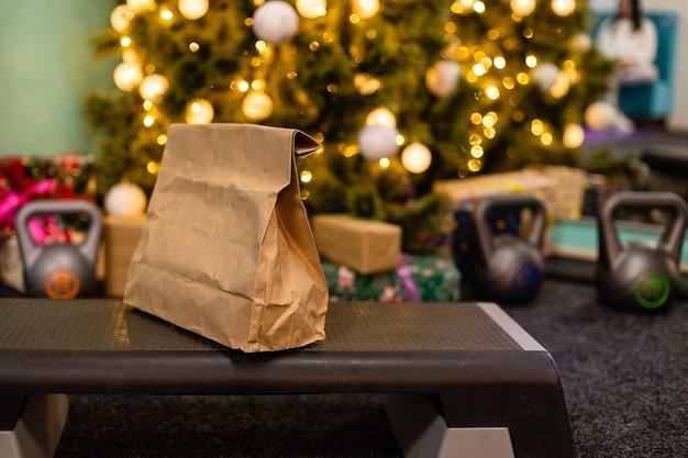 Pacote de entrega com alimentação saudável, peso e halteres no fundo da árvore de natal